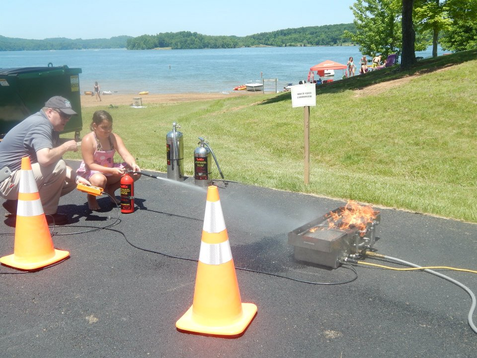 Instructed by a MWCD employee, a young girl learns how to put out this mock fire